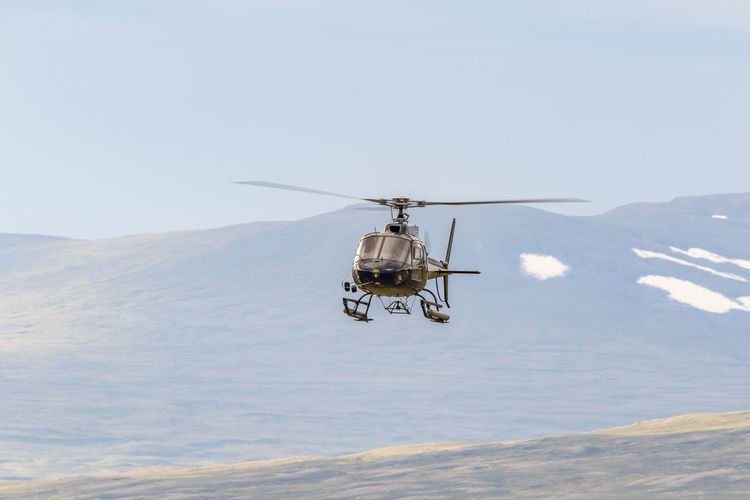 Helicopter in the sky in a wild mountain landscape