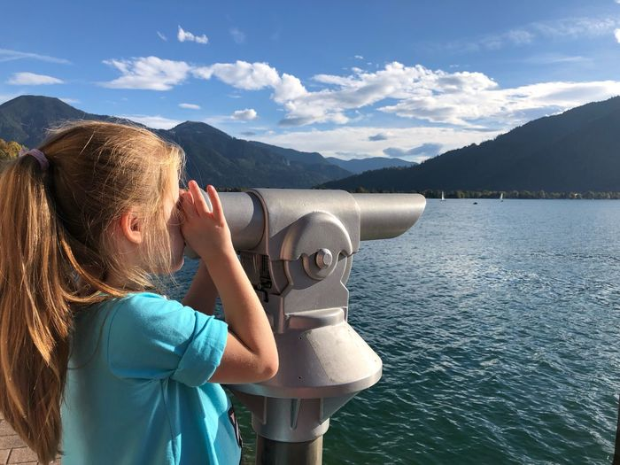 Close-up of girl looking through coin-operated binoculars mountains and sky