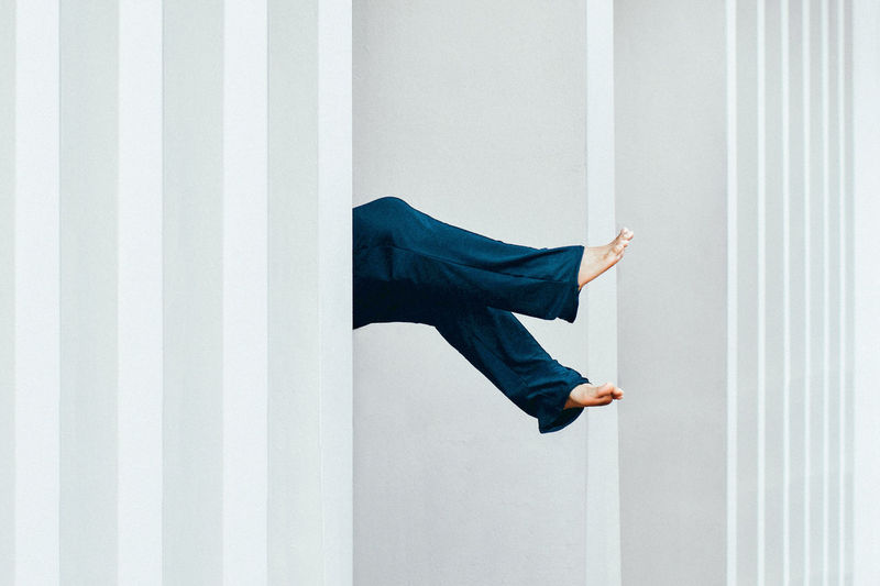 Woman feet floating against the building white wall