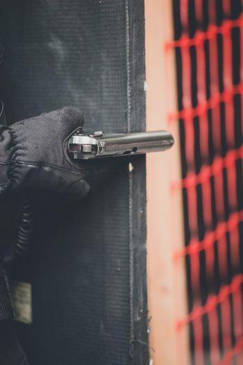 Cropped hand of burglar holding hand gun by door