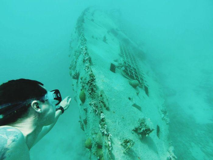 Man deep sea diving and shipwreck
