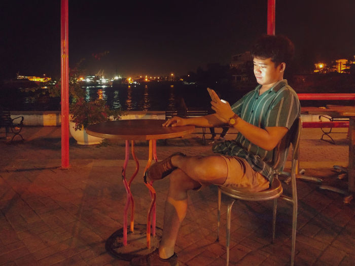 Young man using phone while sitting on table