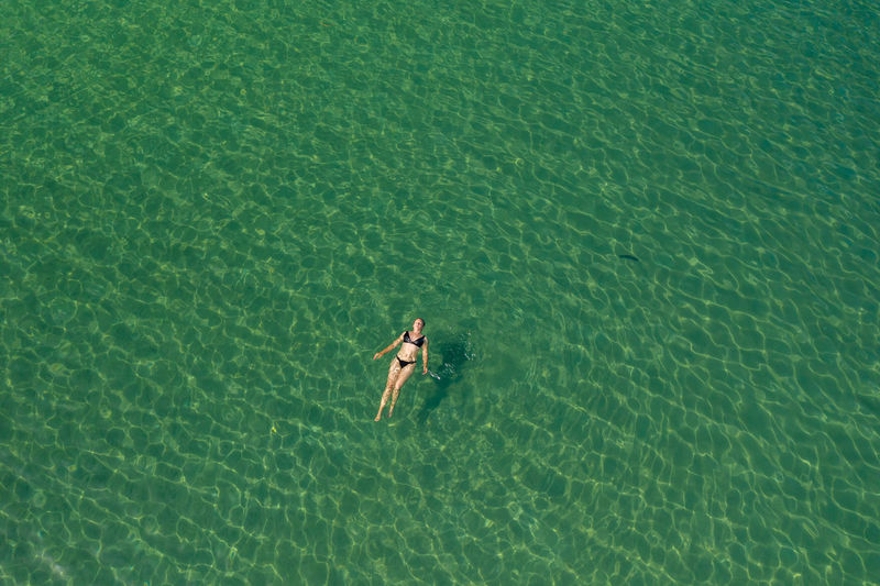 Aerial view of a girl swimming in the adriatic sea, croatia