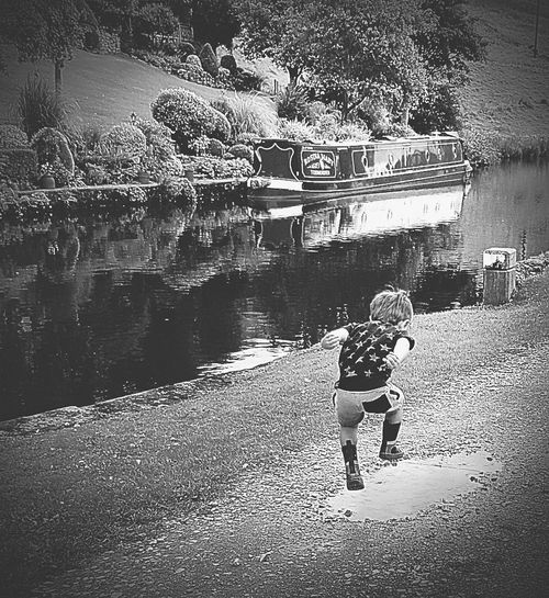 Jumping in puddles Childhood Water Full Length One Person Standing Children Only Boys Outdoors Child Day People Elementary Age One Boy Only Lake Real People Nature Adult Ankle Deep In Water Nautical Vessel The Week On EyeEm Taking Photos Black And White Photography Black&white