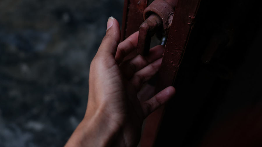 Close-up of person hand touching metallic door