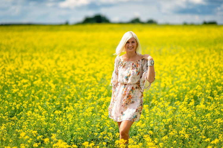 Portrait of woman standing amidst yellow flowers on field