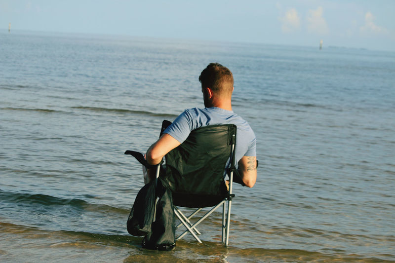 Rear view of man sitting at sea against sky