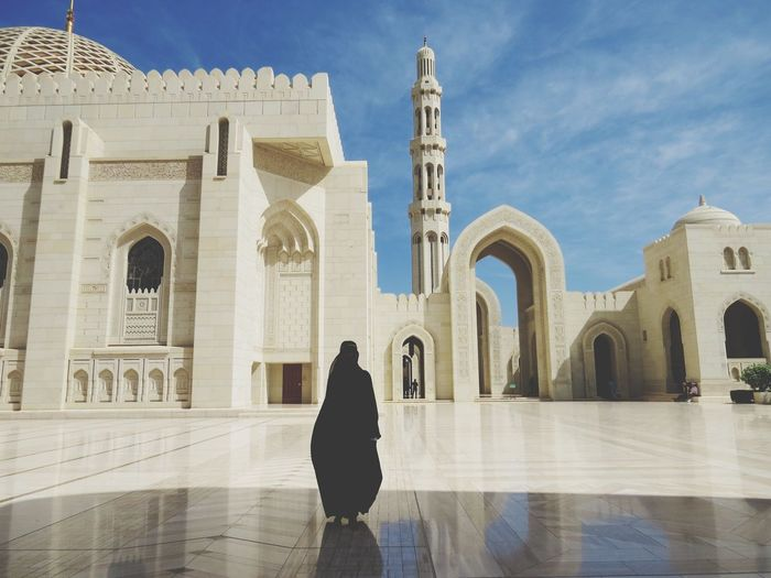Full length rear view of silhouette woman visiting mosque against sky