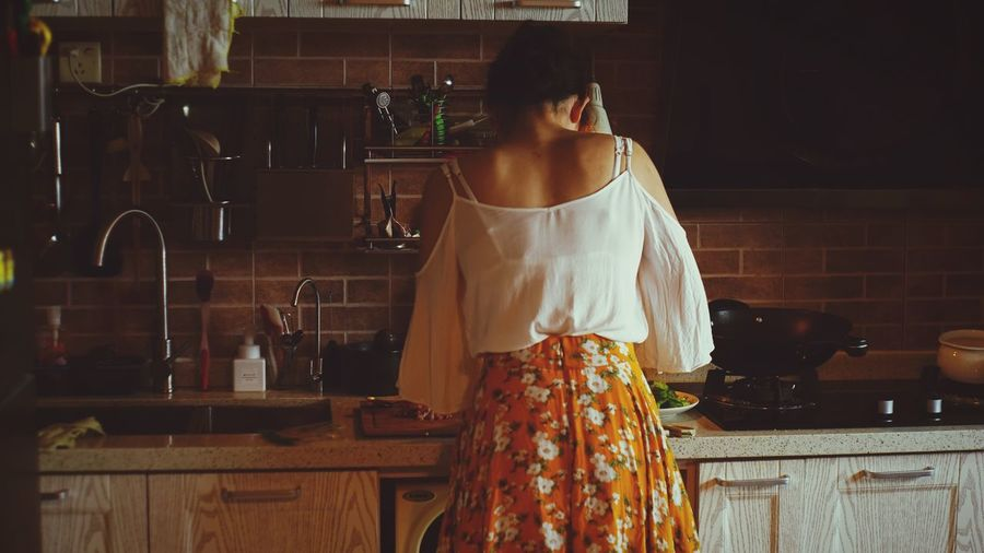 Rear View Of Woman In Kitchen