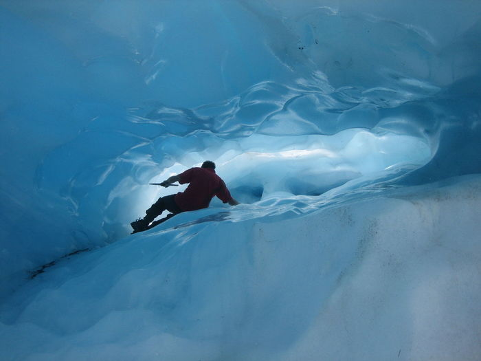 Rear view of man climbing on ice cave