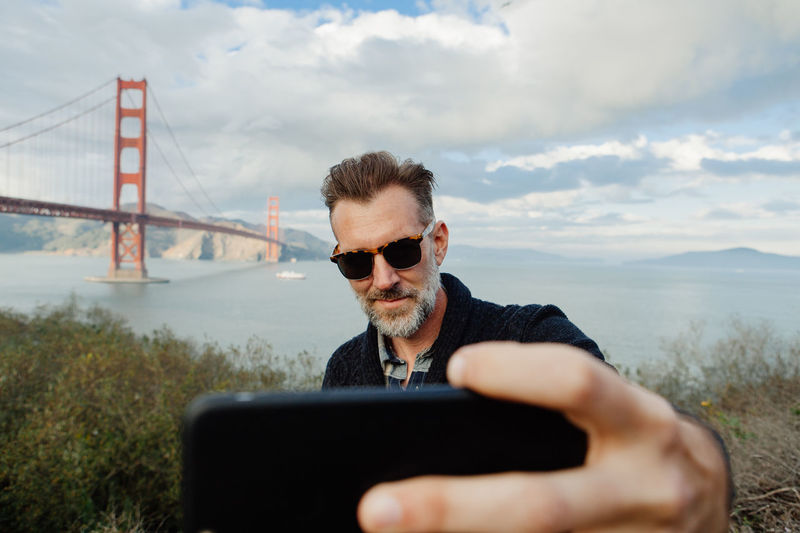 Adult man with beard taking selfie on smartphone with bridge in background