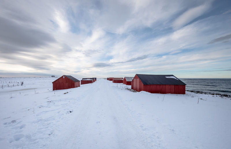 Empty snow covered road amidst barns against cloudy sky