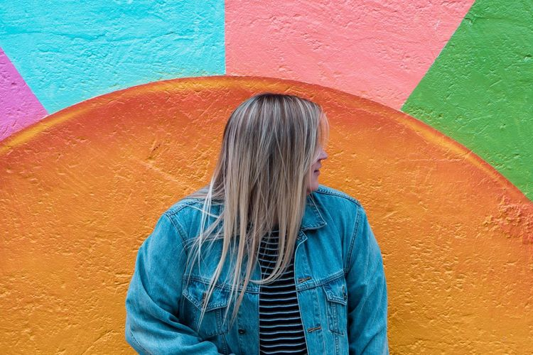 Woman standing against multi colored wall