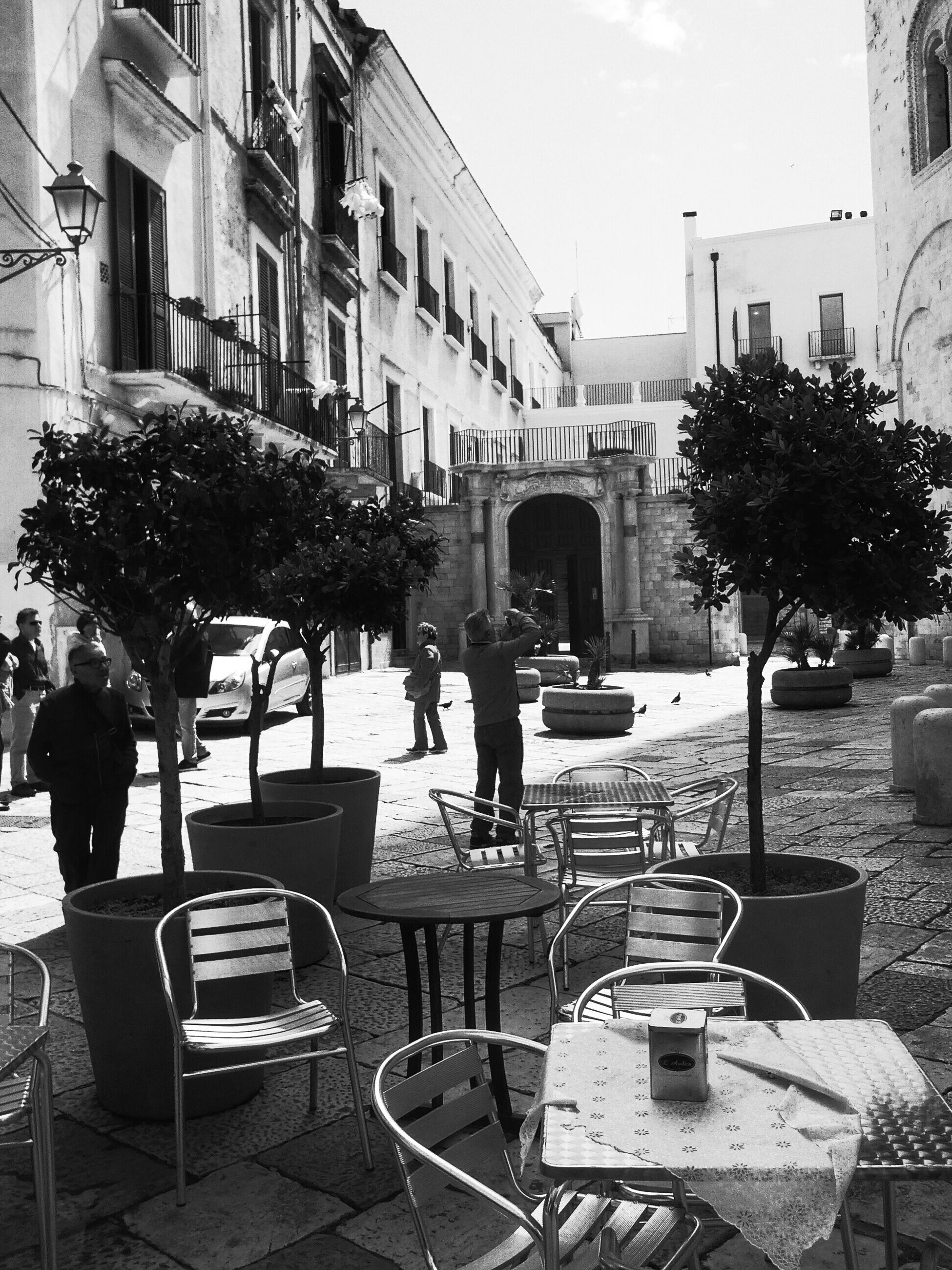 building exterior, chair, architecture, men, built structure, table, sidewalk cafe, city, person, sitting, city life, lifestyles, tree, street, incidental people, bench, restaurant, relaxation, day