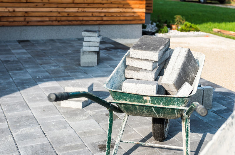 Laying gray concrete paving slabs in house courtyard driveway patio. Wheelbarrows loaded with new tiles or slabs for driveway, sidewalk or patio on leveled foundation base made of sand at public or private residence. Architecture Industrial Masonary New Slabs Wheelbarrow Working Brickwork  Building Exterior Cement Concrete Courtyard  House Installing Laying Leveled Pathway Pavement Paving Paving Stone Paving Stones Private Residence Residence Sand Slab