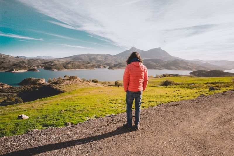 Rear view of woman standing on land by lake against mountains and sky