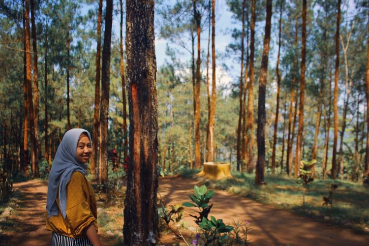 Portrait of smiling young woman standing by trees in forest