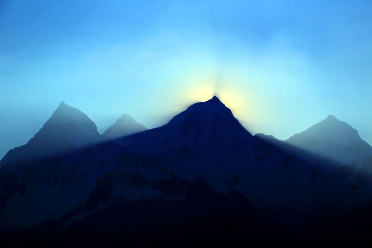 Silhouetted mountain peak against blue sky