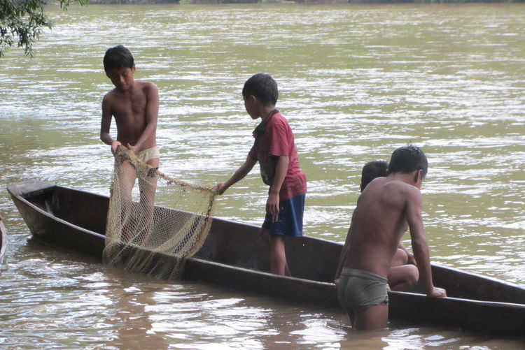 Boys standing on boat in water