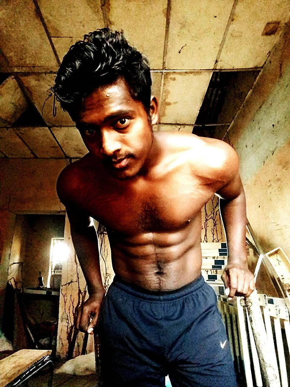 looking at camera, one person, portrait, shirtless, real people, lifestyles, front view, standing, strength, young adult, men, indoors, basement, muscular build, day, one man only, people