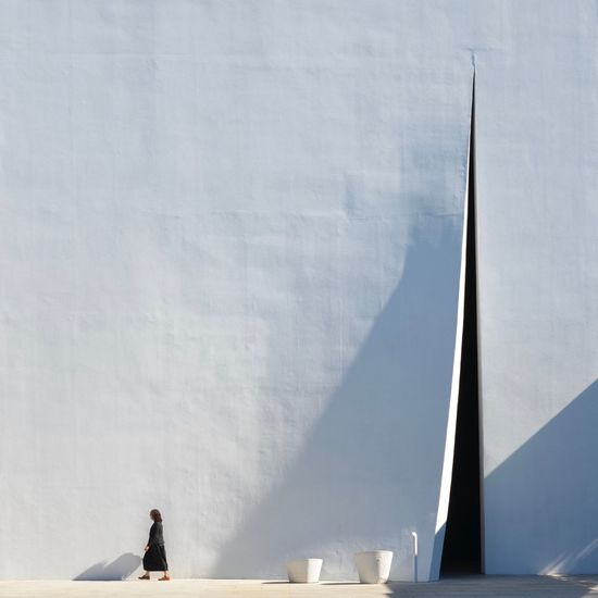 Man on white wall against sky