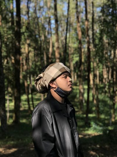 Young man looking away in forest