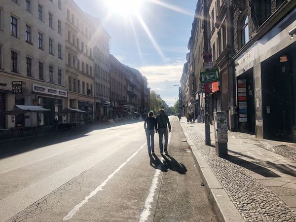 Couple Silhouettes Sunlight City Building Exterior Street Architecture Built Structure Road Lens Flare Real People Sun Sky Shadow Sunny
