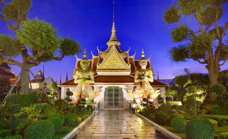 Two statue giant at churches Wat Arun at twilight time, Bangkok Thailand. Architecture Arun Bangkok Thailand. Blue Day Giant Gold Gold Colored No People Outdoors Pagoda Place Of Worship Plant Religion Royalty Sky Spirituality Statue Travel Destinations Tree Wat Pho