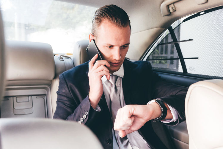 Young Businessman Talking On Mobile Phone While Sitting In Car