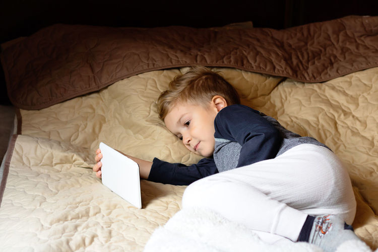 High angle view of boy lying on bed at home