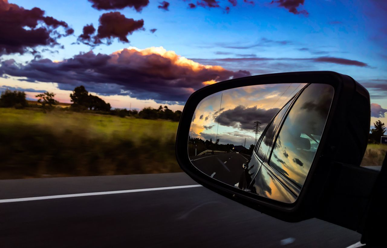 transportation, mode of transportation, sky, cloud - sky, car, motor vehicle, land vehicle, side-view mirror, reflection, road, sunset, mirror, nature, glass - material, motion, no people, outdoors, road trip, on the move, street, vehicle mirror