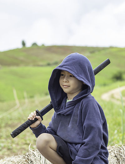 Boy wearing hooded shirt holding sword while sitting against sky