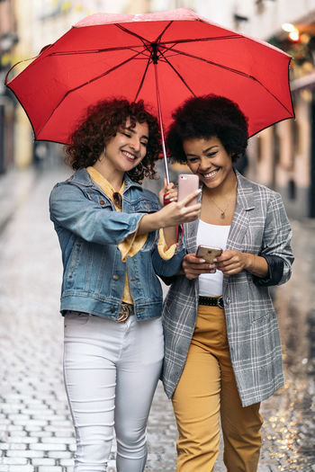 Young couple holding hands while standing on umbrella during rain
