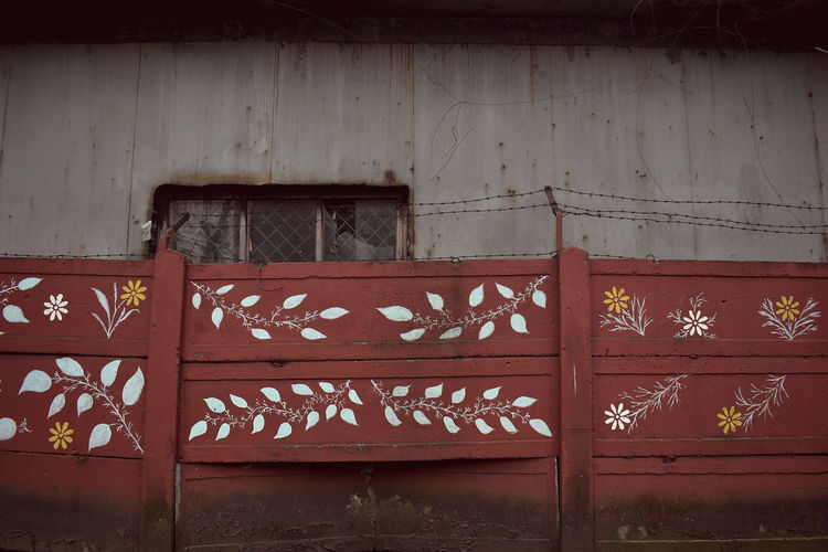 Painted wooden fence outside old building