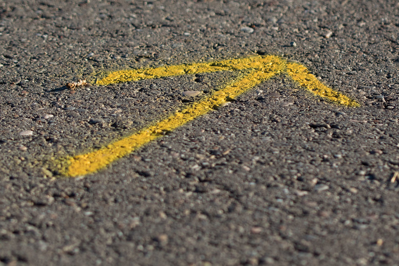 CLOSE-UP OF YELLOW UMBRELLA ON STREET