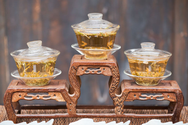 Close-Up Of Herbal Tea In Glass Containers On Table