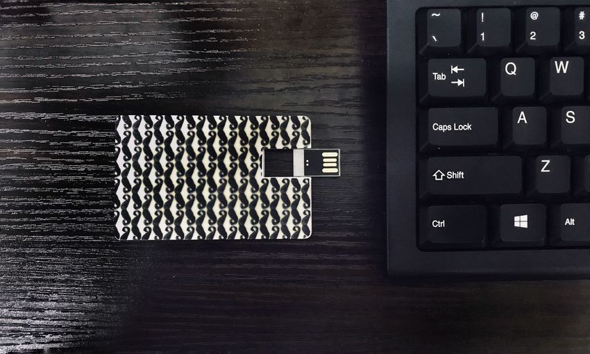 Usb drive or thumbdrive beside computer keyboard Thumbdrive Technology Communication Computer Indoors  Text No People Wireless Technology High Angle View Table Computer Keyboard Black Color Keyboard Computer Equipment Still Life