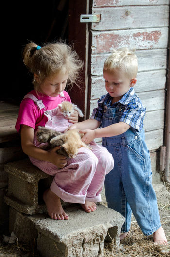young brother and sister play with new kittens on the barn stepsKittens Siblings Animal Themes Animals Blond Hair Bonding Boys Brother And Sister Child Childhood Cute Domestic Animals Family Farm Friendship Full Length Girls Mammal Outdoors Overalls People Pets Real People Sharing  Sitting The Portraitist - 2018 EyeEm Awards