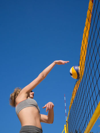 Beach volleyball - athletic woman hits the volleyball over the net Fitness, Activity Attack, Attaktive, Ball Beach Beach Volleyball Beachball Beautiful Bump Dig Female, Hit Jump Matches Net Outdoor Outdoors Play Recreation, Smash  Sport Sportswear, Volleyball Woman