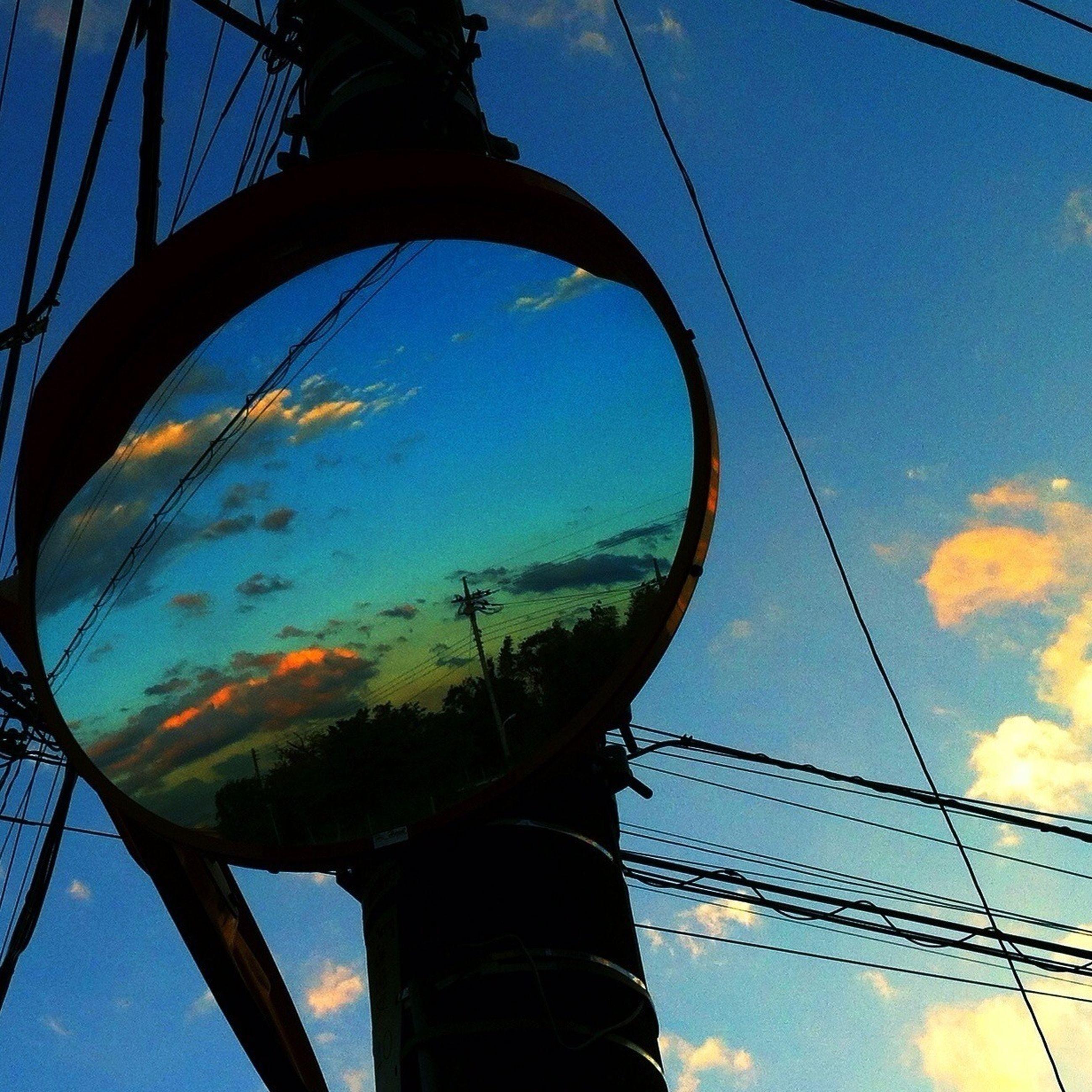 low angle view, sky, blue, part of, cloud - sky, transportation, cloud, connection, power line, metal, electricity, amusement park, outdoors, power supply, electricity pylon, ferris wheel, cable, no people, close-up, circle