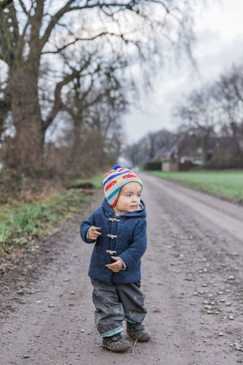 Toddler girl on footpath – Kempen, Germany Adventure Arm Baby Babyhood Bare Boot Building Casual Caucasian Cheerful Child Childhood Coat Curiosity Cute Dirt Duffle Coat Exploring Field Finger First Steps Footpath Front View Full Length Germany Gesturing Girl Hand Happy Hiking House Innocence Jacket Joy Messy Mud Nature One Outdoors Pants People Pointing Portrait Rural Standing Toddler  Tree Walking Wanderlust Winter One Person Day Clothing Focus On Foreground Road Plant Casual Clothing Real People Warm Clothing