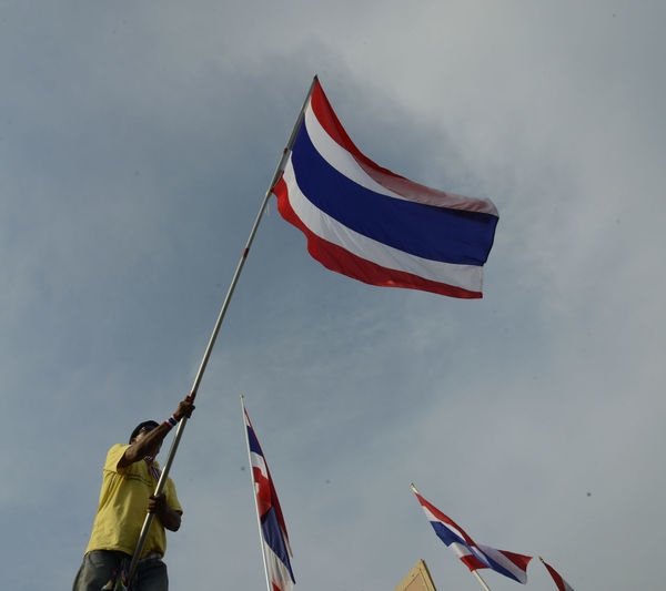 Low Angle View Of Man With Thai Flag Protesting Against Sky