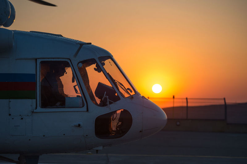 Helicopter on runway against sky during sunset