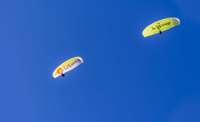 Low angle view of paragliding against blue sky