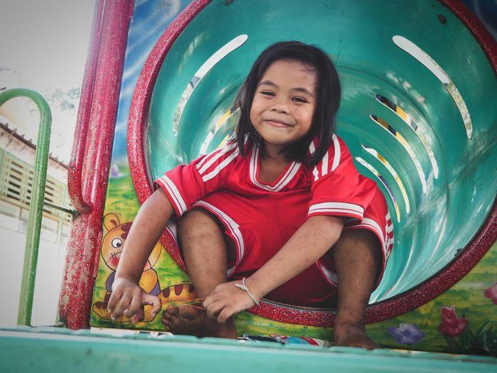 Portrait of happy girl sitting on slide