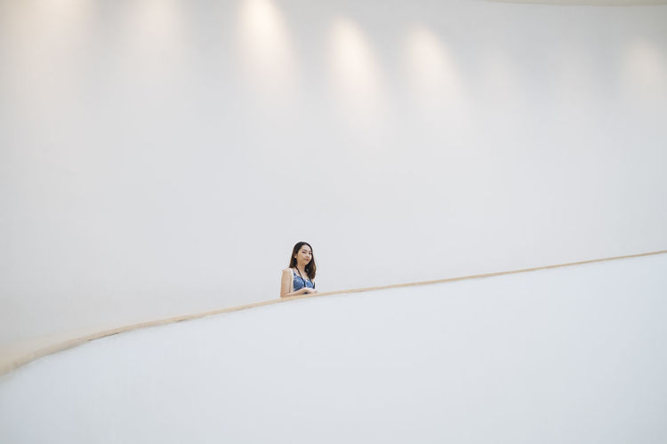 Low angle view of woman standing against white wall