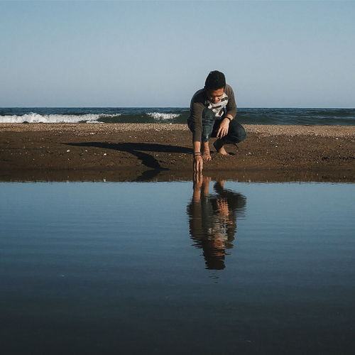 Young man crouching at sea shore against sky