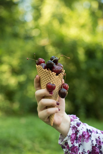 Close-up of woman holding cherries in waffle cone