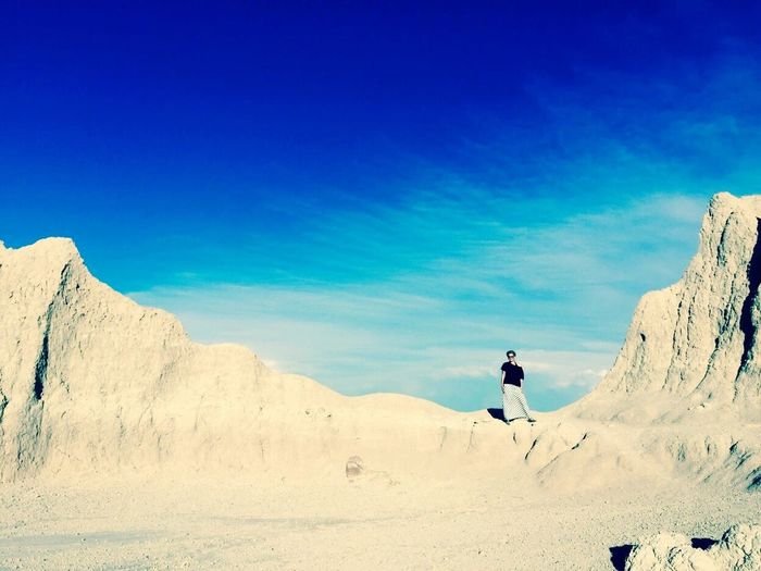 Woman standing on rock formation against sky at badlands national park