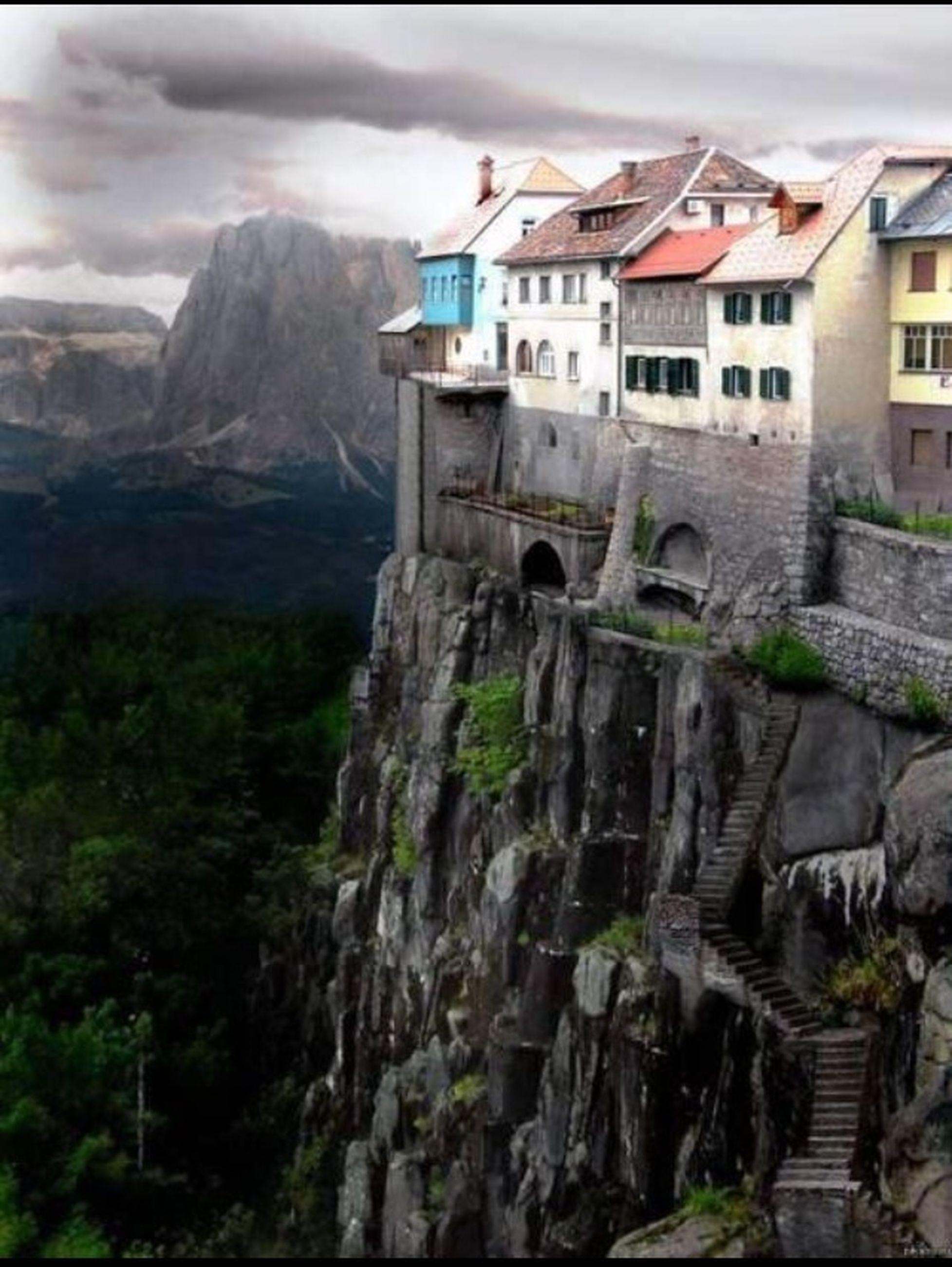 mountain, architecture, built structure, building exterior, sky, house, mountain range, rock - object, low angle view, railing, day, nature, outdoors, cloud - sky, rock formation, hill, no people, residential structure, rocky mountains, steps